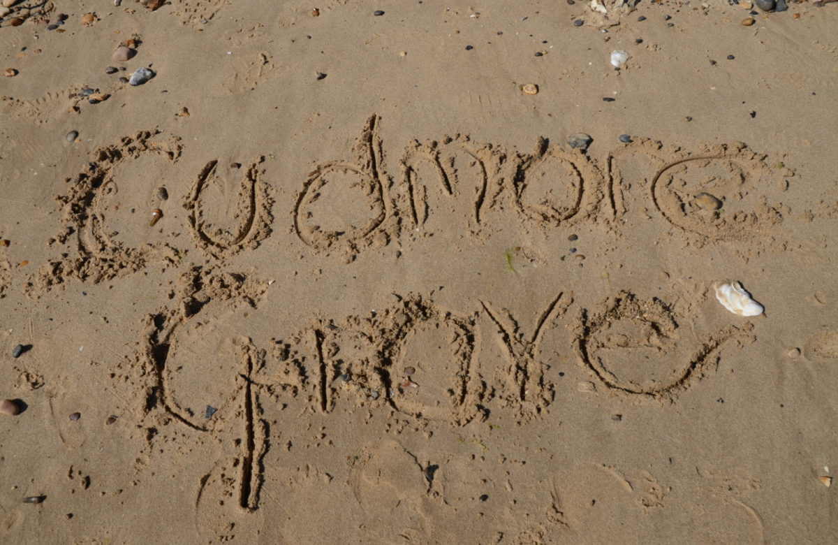 The words Cudmore Grove written in the sand