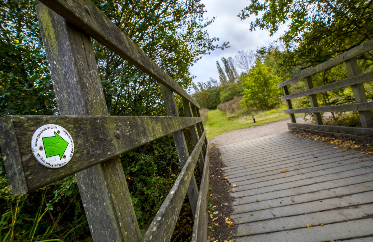 A wooden bridge and trail sign