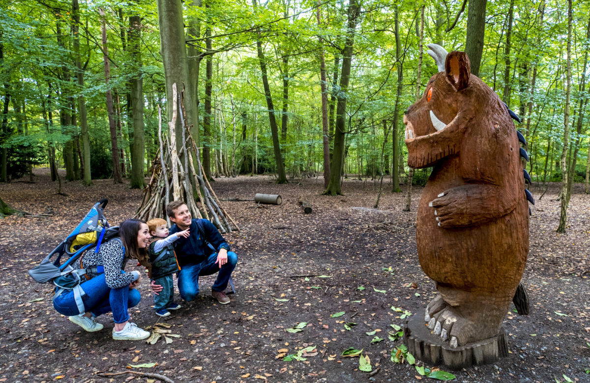 A family admiring a carving of The Gruffalo