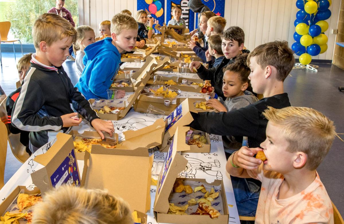 A children's birthday party enjoying the birthday tea and cake
