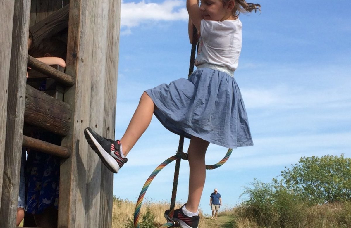 A girl climbing up a rope