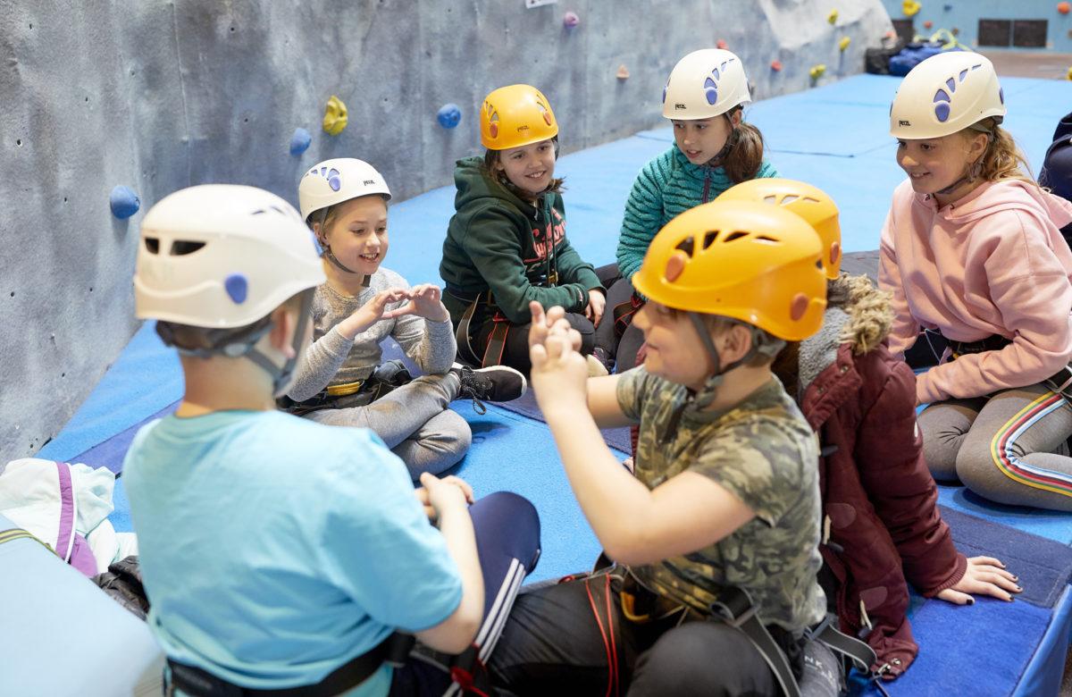 Children sitting near a climbing wall