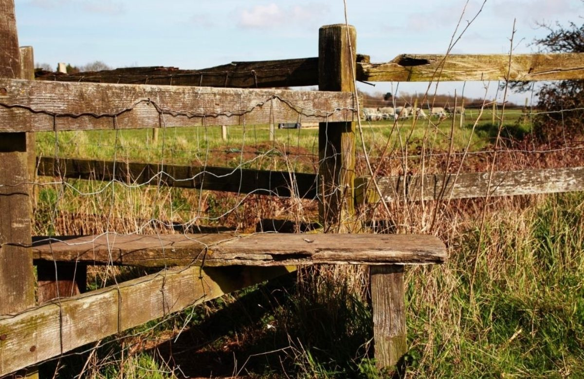 A wooden sty over a wooden fence