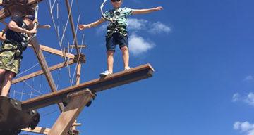 A child balancing at Sky Ropes
