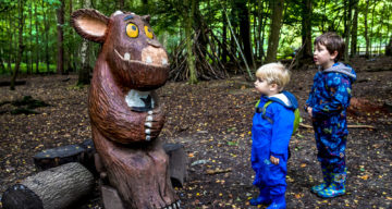 Two boys looking at a wooden sculpture of The Gruffalo