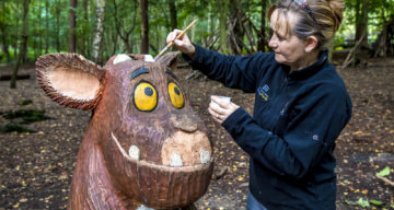 An artist painting a wooded sculpture of The Gruffalo