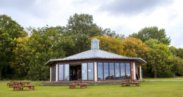 A modern glass building surrounded by picnic benches