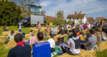 Audience sat on hay bales and cinema screen