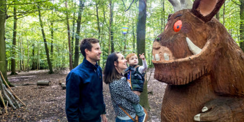 A family admiring a wooden carving of The Gruffalo