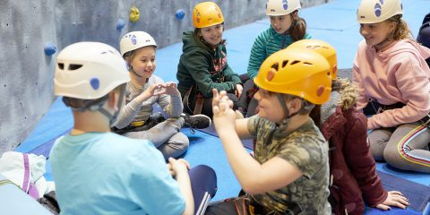 Children sitting near a climbing wall