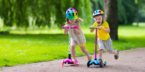 A young boy and girl on scooters